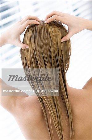 Junge Frau mit langen nassen Haaren, Blick von der Rückseite, close up (Studio)