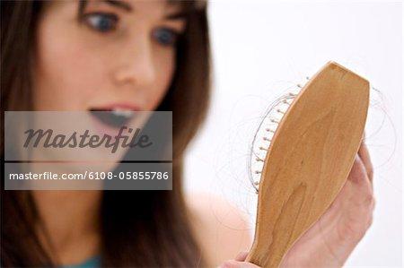 Portrait d'une jeune femme tenant une brosse à cheveux