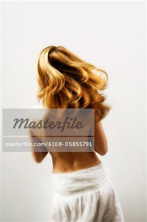 Junge Frau mit blondem Haar, Blick von der Rückseite, verschwommene Bewegung (Studio)