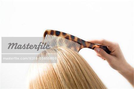 Portrait d'une jeune femme peignant ses cheveux, close up, studio