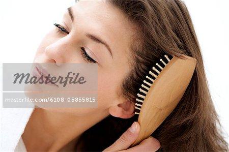 Portrait d'une jeune femme se brosser ses cheveux