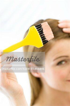 Porträt einer jungen Frau färben ihr Haar, wenig Pinsel in der hand