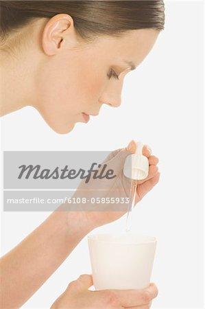 Femme avec verre et huile essentielle
