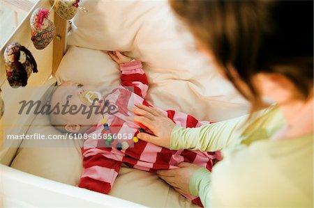 Mère caresser son bébé au lit avec couette
