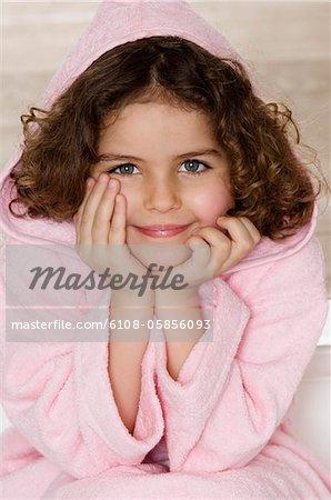 Petite fille en peignoir de bain en regardant la caméra