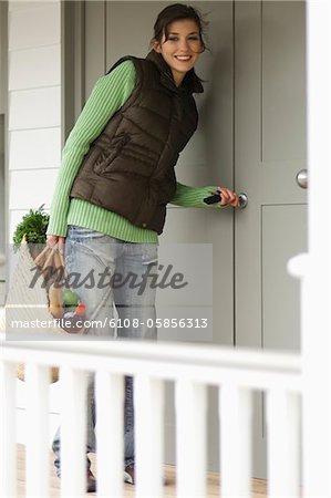 Jeune femme avec panier d'achat, déverrouillage de porte