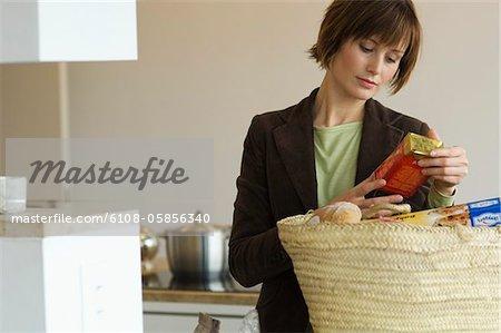 Junge Frau entleeren Warenkorb in der Küche