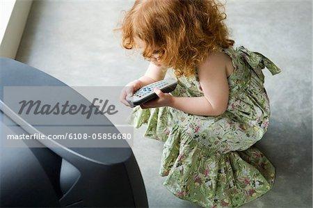 Petite fille accroupie devant la télévision, holding de contrôle à distance, élevé vue