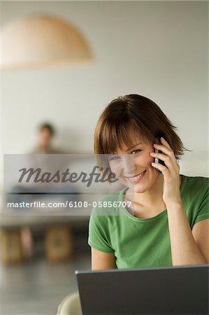 Lächelnde Frau mit Laptop und Handy, Mann im Hintergrund