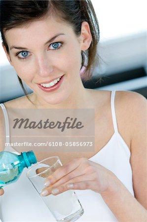 Portrait d'une jeune femme souriante, verser l'eau dans un verre