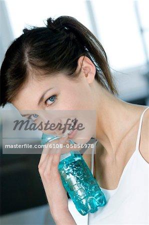Portrait d'une jeune femme souriante tenant une bouteille d'eau minérale