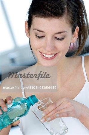 Portrait jeune femme souriante verser l'eau dans un verre