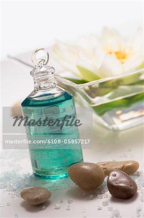 Bouteille d'huile essentielle, peebles et fleur de lys d'eau, gros plan