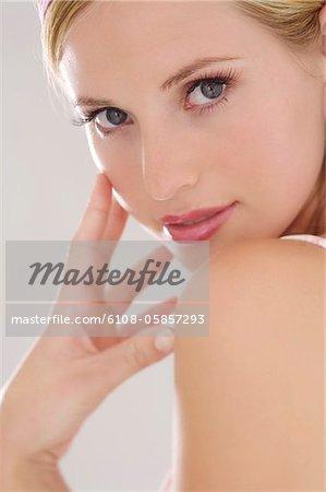 Portrait d'une jeune femme regardant la caméra, la main sur sa joue, à l'intérieur (studio)