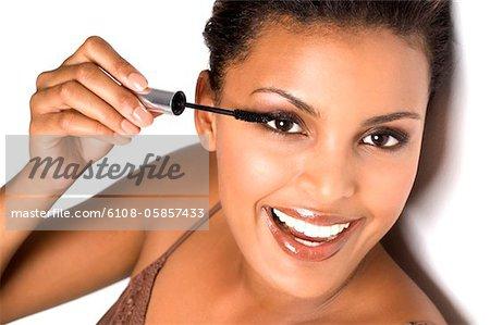 Portrait of a smiling woman applying mascara