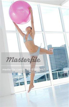 Young woman in bikini, jumping, holding big pink balloon