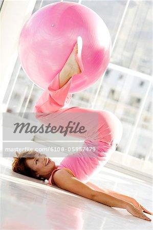 Junge lächelnde Frau auf Rücken, liegend halten große rosa Ballon mit Füßen