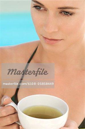Porträt der jungen Frau hält eine Tasse grüner Tee, im freien