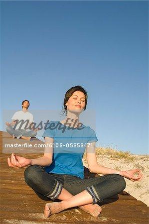 Junges Paar in Yoga-Haltung, im freien