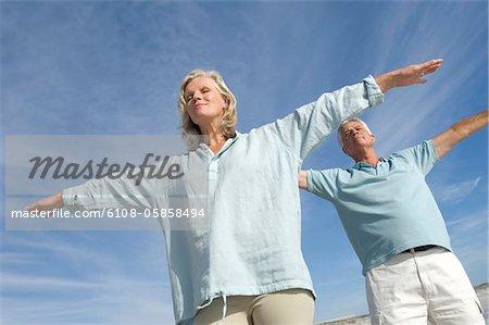 Couple en attitude d'yoga sur la plage, en plein air