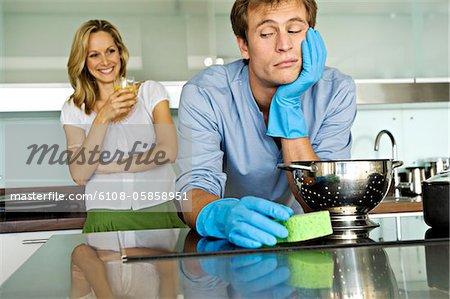 Femme souriante regardant bouder homme tenant une éponge