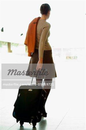 Vue arrière d'une femme d'affaires tirant ses bagages dans un aéroport