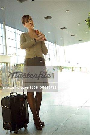 Femme d'affaires permanent avec ses bagages à un salon de l'aéroport