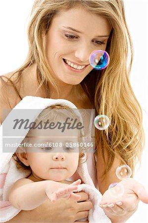 Gros plan d'une jeune femme et son fils jouer avec des bulles de savon