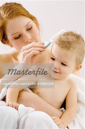 Nahaufnahme einer jungen Frau, die Haare ihres Sohnes zu kämmen