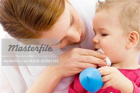 Gros plan d'une jeune femme en essuyant la bouche de son fils