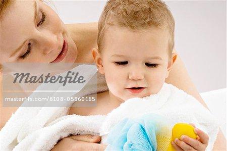 Gros plan d'une jeune femme, son fils d'emballage dans une serviette