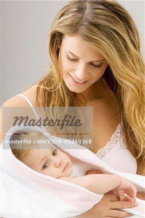 Gros plan d'une jeune femme, son fils d'emballage dans une serviette et souriant