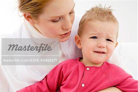 Gros plan d'une jeune femme portant son fils qui pleure