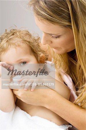 Gros plan d'une jeune femme, essuyer la bouche de son fils