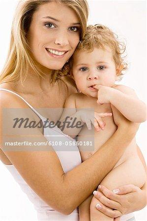 Portrait d'une jeune femme portant son fils et souriant