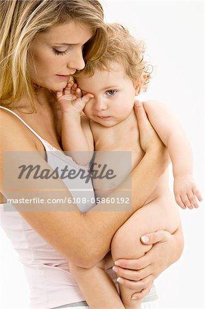 Profil de côté d'une jeune femme portant son fils