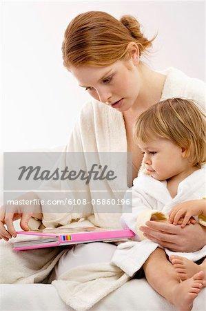Gros plan d'une jeune femme assise avec son petit garçon et en regardant un livre d'images