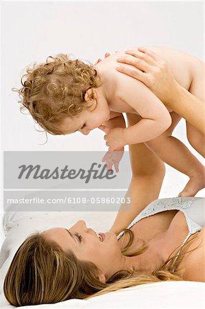 Gros plan d'une jeune femme de mentir et de jouer avec son fils