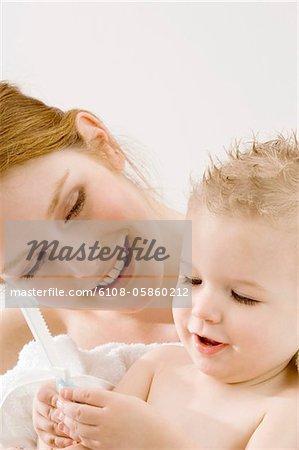 Gros plan d'un petit garçon tenant un peigne et assis avec sa mère