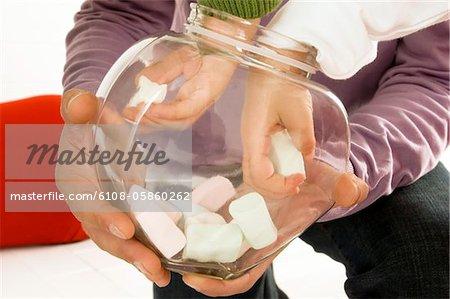 Les enfants ramasser les guimauves d'un contenant de verre tenue par son père