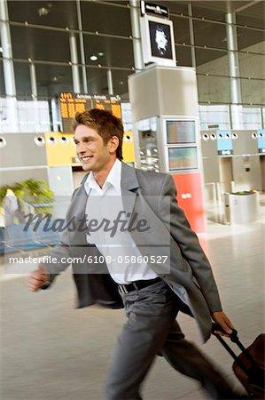 Profil de côté d'un homme d'affaires se précipiter avec ses bagages dans un aéroport