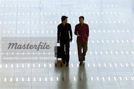 Mid homme adulte qui marche avec un jeune homme dans un aéroport