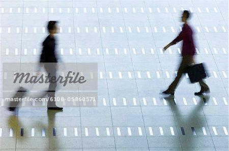 Vue grand angle des deux hommes marchant dans un hall d'aéroport