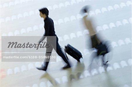 Vue grand angle de deux passagers à pied dans un aéroport