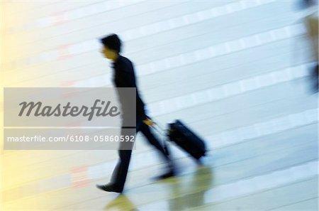 Vue d'angle élevé d'un homme tirant ses bagages à un hall de l'aéroport