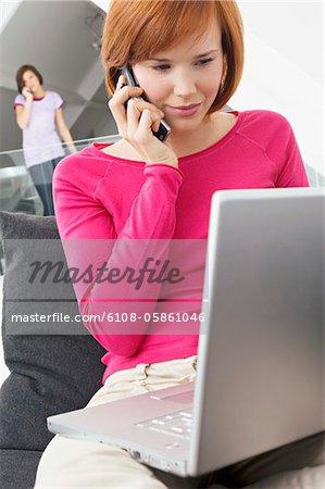 Gros plan d'une jeune femme à l'aide d'un ordinateur portable et de parler sur un téléphone mobile