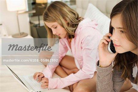 Mädchen sprechen auf ein Mobiltelefon und ihre Schwester arbeitet an einem laptop