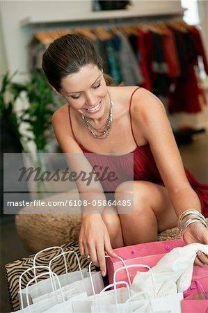 Beim Überprüfen der Einkaufstaschen in einer Boutique lächelnde Frau