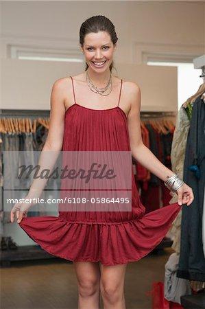 Halten Sie ihr Kleid in eine Boutique und lächelnde Frau