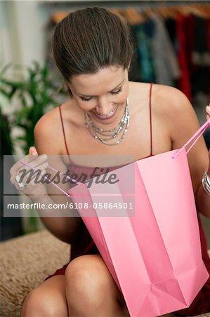 Beim Überprüfen einer Einkaufstasche in einer Boutique lächelnde Frau